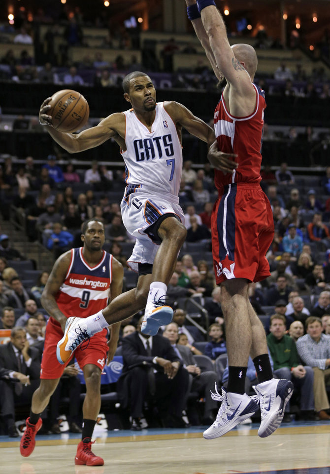 Photo - Charlotte Bobcats' Ramon Sessions, center, drives between Washington Wizards' Marcin Gortat, right, and Martell Webster (9) during the first half of an NBA basketball game in Charlotte, N.C., Tuesday, Jan. 7, 2014. (AP Photo/Chuck Burton)