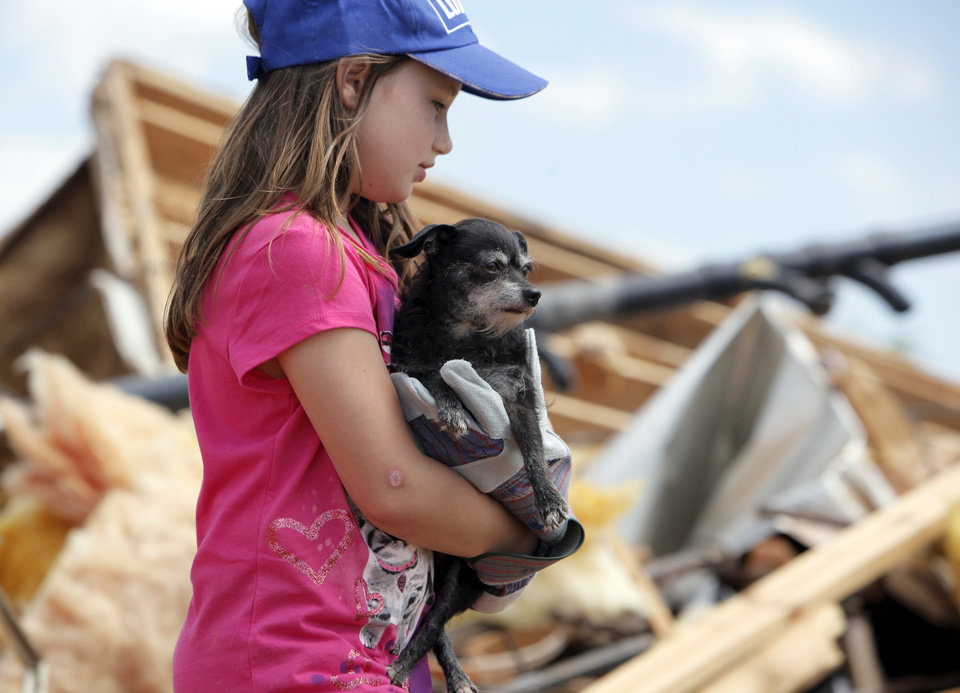 Alyssa Coleman, 8, carries her dog Blackie Chan through the debris of what was her home in the Hide-A-Way Mobile Home Park in Woodward, Okla., Monday, April 16, 2012. A tornado struck the town early Sunday morning. Photo by Nate Billings, The Oklahoman