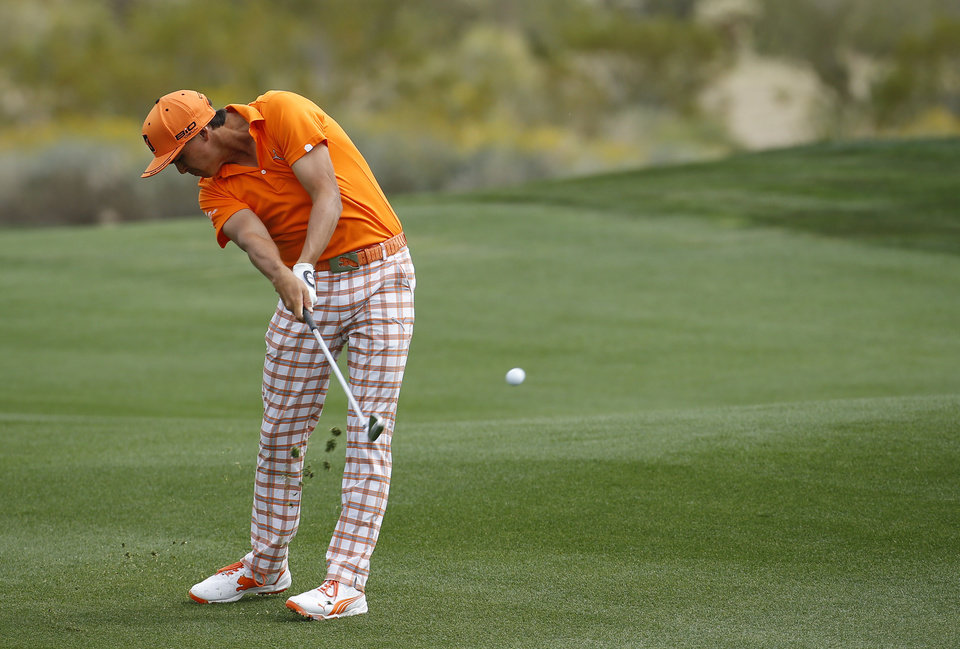 Photo - Rickie Fowler hits from the fairway on the second hole in his consolation match against Ernie Els, of South Africa, during the Match Play Championship golf tournament on Sunday, Feb. 23, 2014, in Marana, Ariz. (AP Photo/Matt York)