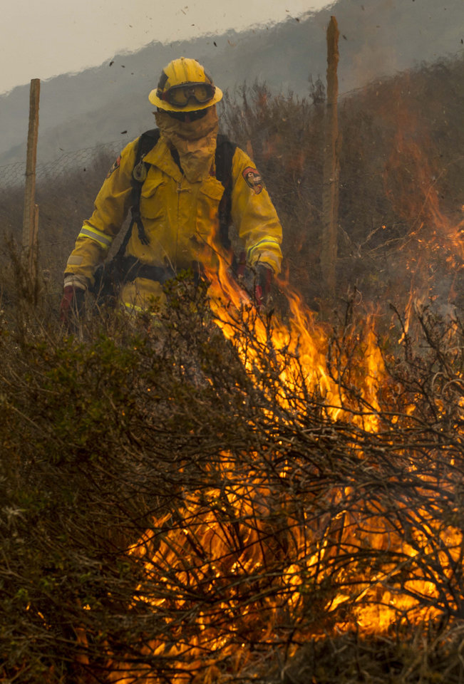 A firefighter sets a backfire to protect the farmland along a hillside in Point Mugu , Calif. Friday, May 3, 2013. A huge Southern California wildfire carved a path to the sea and burned on the beach Friday, but firefighters got a break as gusty winds turned into breezes. Temperatures remained high, but humidity levels were expected to soar as cool air moved in from the ocean and the Santa Ana winds retreated. (AP Photo/Ringo H.W. Chiu) ORG XMIT: CARC112