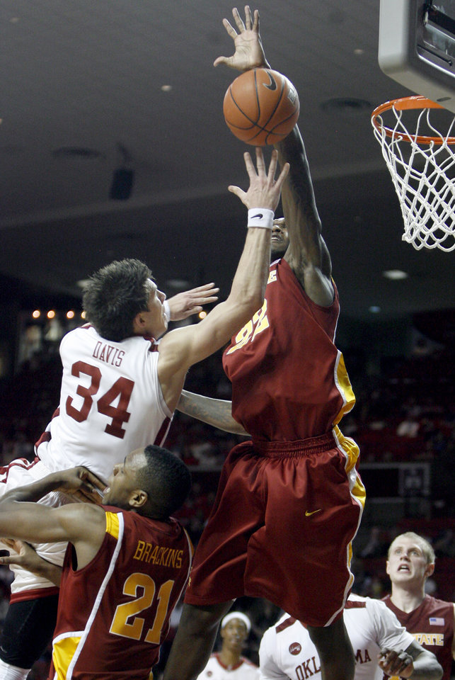 Photo - OU's Cade Davis (34) shoots as Iowas State's Craig Brackins (21) and LaRon Dandy (22) defend during the college men's basketball game between the University of Oklahoma and Iowa State, Wednesday, Jan. 27, 2010, at the Lloyd Noble Center in Norman, Okla. Photo by Sarah Phipps, The Oklahoman.