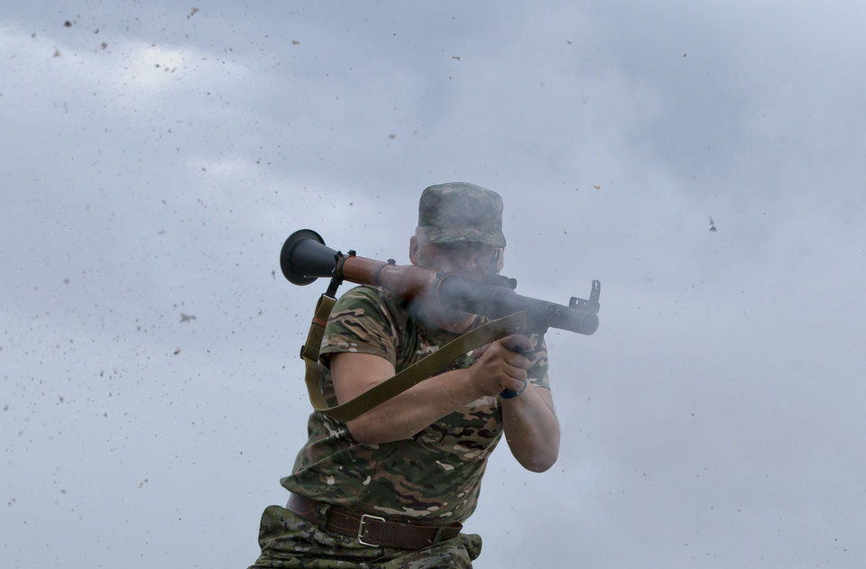 Photo - A pro-Russian rebel fires a rocket propelled grenade on the rooftop of an apartment building during clashes with Ukrainian troops on the outskirts of Luhansk, Ukraine, Monday, June 2, 2014. Hundreds of pro-Russia insurgents attacked a border guard base in eastern Ukraine on Monday, with some firing rocket-propelled grenades from the roof of a nearby residential building. At least five rebels were killed when the guards returned fire, a spokesman for the border guard service said.(AP Photo/Vadim Ghirda)