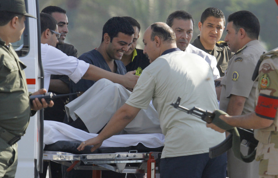 Photo - Egyptian medics share a laugh with former Egyptian President Hosni Mubarak, 85, as they escort him into an ambulance after after he was flown by a helicopter ambulance to the Maadi Military Hospital from Torah prison in, Cairo, Egypt, Thursday, Aug. 22, 2013. Egypt's ousted leader Hosni Mubarak has been released from jail and taken to military hospital in Cairo. (AP Photo/Amr Nabil)