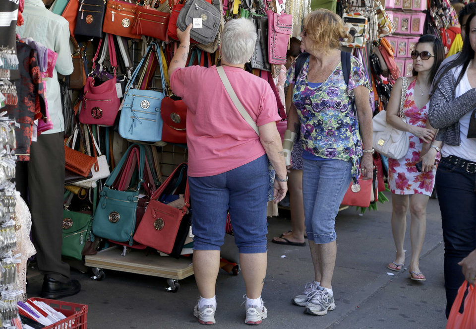 Women looks over a display of purses on Canal Street in New York, Tuesday, June 4, 2013. Bargain hunters from around the world flock to Manhattan's Chinatown for legally sold bags, jewelry and other accessories bursting onto sidewalks from storefronts along Canal Street. (AP Photo/Seth Wenig)