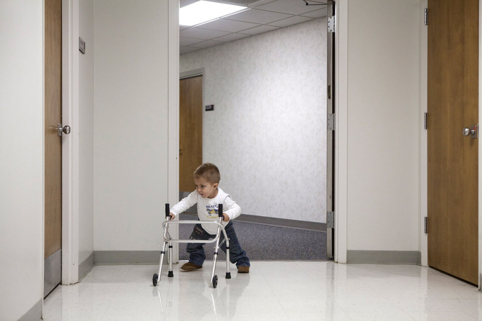 Photo - Two-year-old Andre de Guisti uses his walker to head down the halls of Covenant HeathCare Cooper, in Saginaw, on Wednesday, Jan. 9, 2013. De Guisti was born with sacral angenesis which caused nerve damage in his lower spine, knee problems, two dislocated hips and club feet. Andre's parents, Dino and Amore de Guisti had heard from doctors back home in Johannesburg, South Africa that their only option was to amputate his legs. A doctor from Saginaw who makes regular trips to South Africa to work at a clinic and hunt heard Andre's story and offered to help. Two years ago Andre had surgery and although he has a lot of physical therapy ahead of him, he is expected to be able to walk someday. (AP Photo/The Saginaw News, Clay Lomneth )