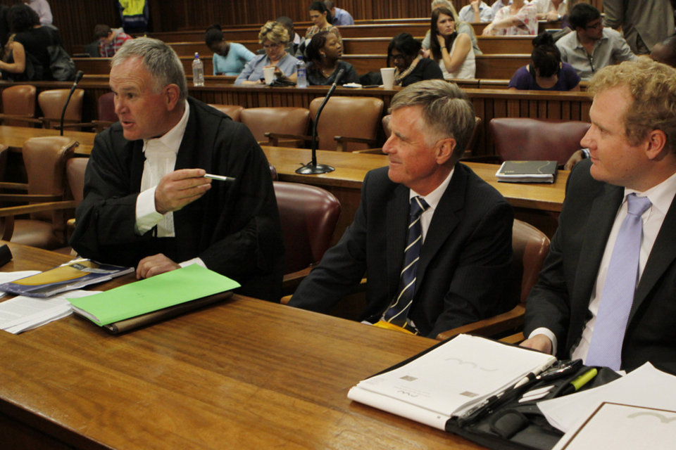 Photo - The defense team for Oscar Pistorius, led by Barry Roux, left, prepare for an appeasl against bail conditions in the Pretoria, South Africa high court, Thursday, March 28, 2013. Pistorius is  charged with the shooting death of his girlfriend Reeva Steenkamp last month. (AP Photo/Denis Farrell)
