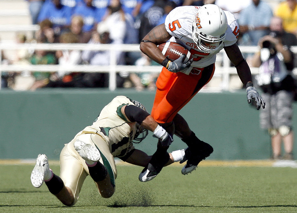 Photo - OSU's Keith Toston is tripped up by Baylor's Mike Hicks (17) during the college football game between Baylor University and Oklahoma State University (OSU) at Floyd Casey Stadium in Waco, Texas, Saturday, Oct. 24, 2009.  Photo by Sarah Phipps, The Oklahoman