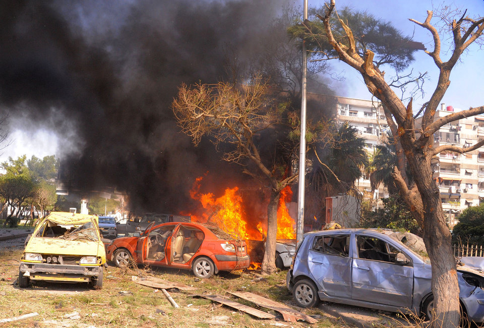 Photo - This photo released by the Syrian official news agency SANA, shows flames and smoke rising from burned cars after a huge explosion that shook central Damascus, Syria, Thursday, Feb. 21, 2013. A car bomb shook central Damascus on Thursday, exploding near the headquarters of the ruling Baath party and the Russian Embassy, eyewitnesses and opposition activists said. (AP Photo/SANA)