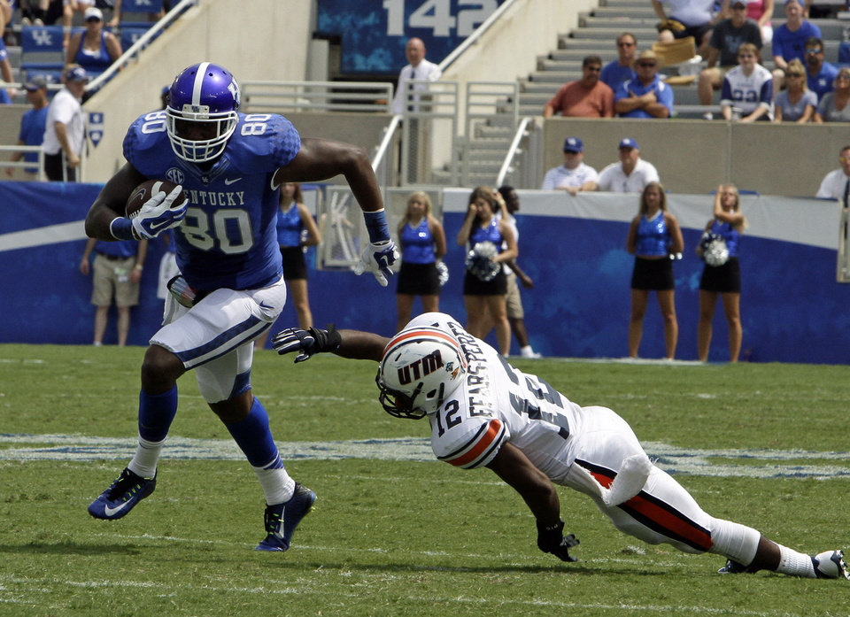 Photo - Kentucky tight end Ronnie Shields (80), runs away from Tennessee-Martin defender Taino Fears-Perez (12) after a reception in their NCAA college football game in Lexington, Ky., Saturday, Aug. 30, 2014. Kentucky beat Tennessee-Martin 59-14. (AP Photo/Garry Jones)