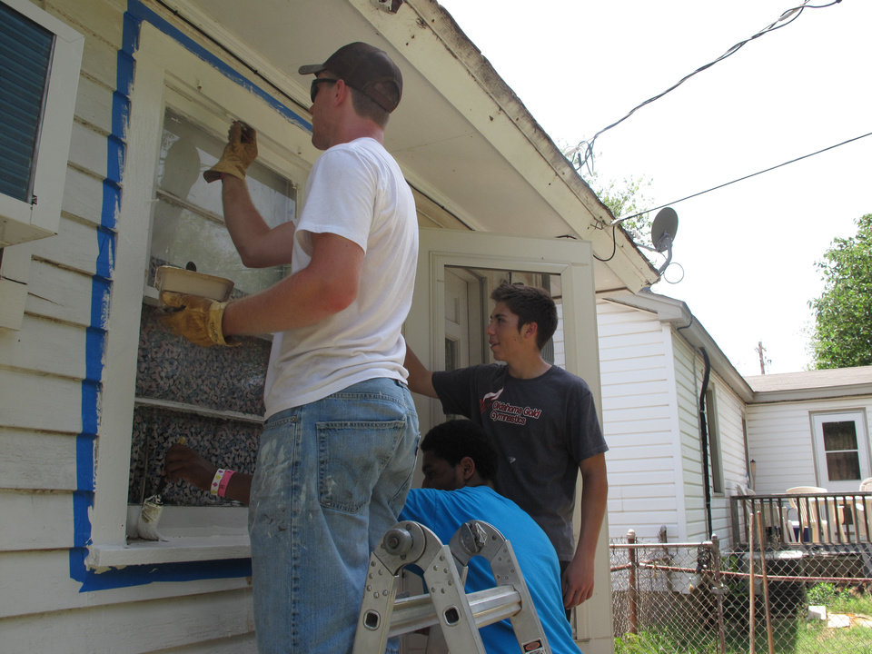 Photo - Dustin Preston, 18, of Main Street Baptist Church in Greenfield, Mo., paints the exterior of an Edmond home Monday with the help of Caleb MCPherson, 15, from Gateway Assembly of God in Southlake, Texas, Church, and Trent Sanders, 13, also a member of Gateway.  The Oklahoman - CARLA HINTON