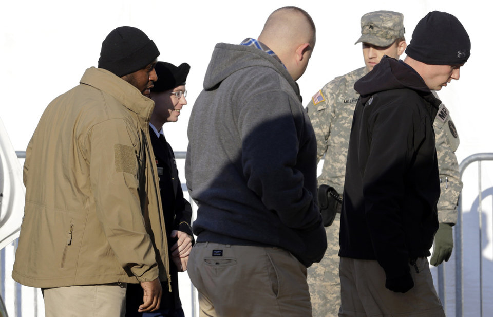 Photo -   Army Pfc. Bradley Manning, second from left, is escorted from a security vehicle to a courthouse in Fort Meade, Md., Wednesday, Nov. 28, 2012, for a pretrial hearing. Manning is charged with aiding the enemy by causing hundreds of thousands of classified documents to be published on the secret-sharing website WikiLeaks. (AP Photo/Patrick Semansky)