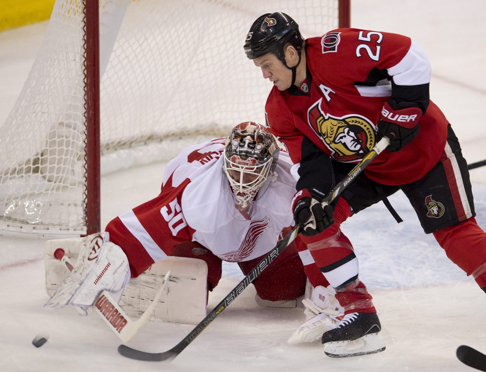 Photo - Ottawa Senators right wing Chris Neil (25) pressures Detroit Red Wings goalie Jonas Gustavsson for control of the puck during first period NHL action Sunday Dec. 1, 2013, in Ottawa, Ont.  (AP Photo/The Canadian Press, Adrian Wylde)