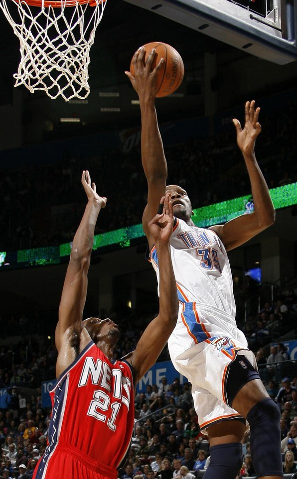 Photo - Oklahoma CIty's Kevin Durant goes to the basket past New Jersey's Travis Outlaw during the NBA basketball game between the Oklahoma City Thunder and the New Jersey Nets at the Oklahoma City Arena, Wednesday, Dec. 29, 2010.  Photo by Bryan Terry, The Oklahoman