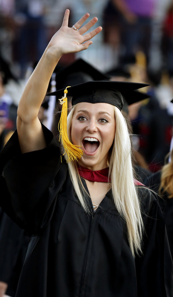 Photo -  At left: University of Oklahoma graduate Erin Tsambikos, of Edmond, waves upon entering Gaylord Family — Oklahoma Memorial Stadium at the May 2014 commencement ceremony. Photo by Steve Sisney, The Oklahoman Archives   STEVE SISNEY -  THE OKLAHOMAN