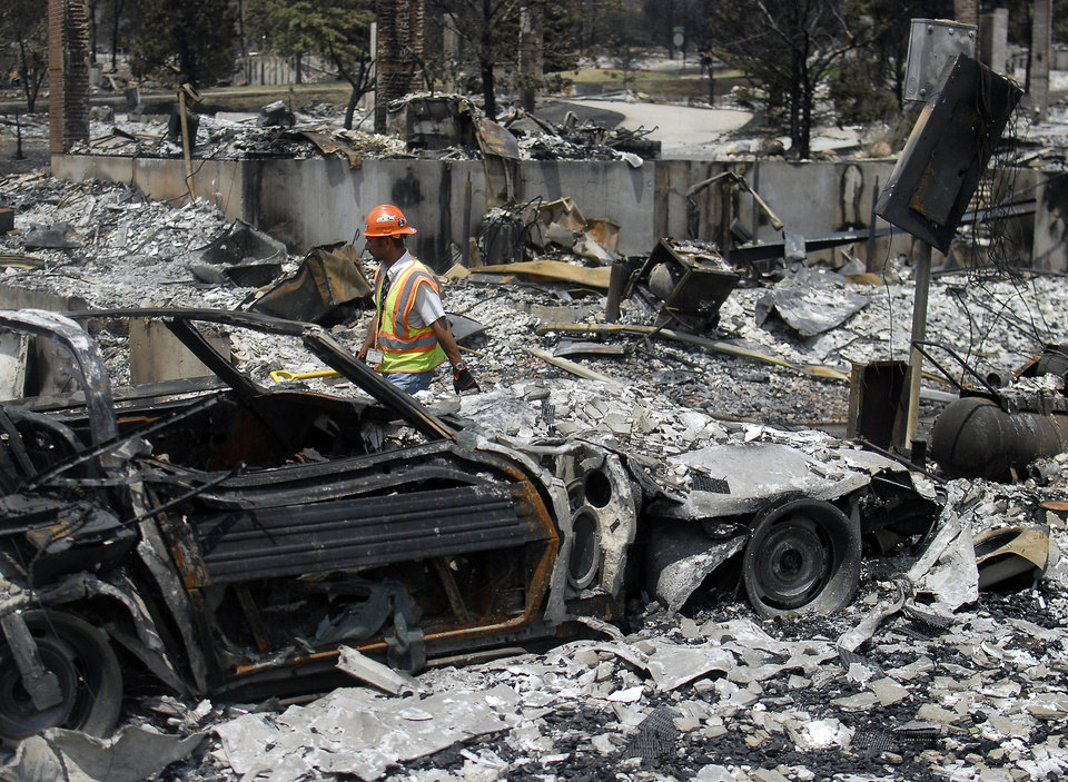 Photo - A utilities worker walks through homes destroyed by the Waldo Canyon Fire in the Mountain Shadows neighborhood of Colorado Springs, Colo., on Monday, July 2, 2012. So far, the blaze, now 45 percent contained, has damaged or destroyed nearly 350 homes. (AP Photo/Bryan Oller) ORG XMIT: COBO105