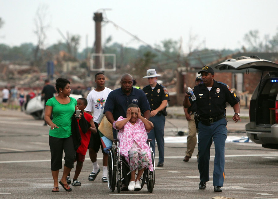 Photo - A misplaced family is assisted by emergency responders Wednesday, April 27, 2011, near in Tuscaloosa, Ala. A wave of severe storms laced with tornadoes strafed the South region. (AP Photo/Tuscaloosa News, Dusty Compton)