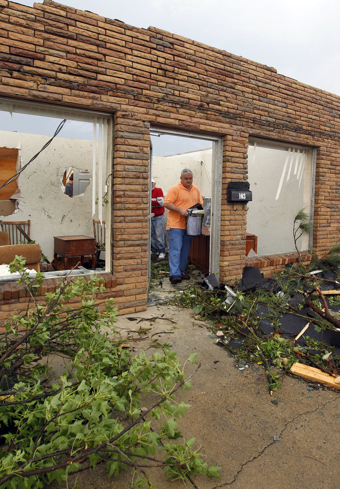 Photo - Mark Richter carries some belongings out of what is left of his wife's law firm after a tornado hits downtown Culman, Ala., on Wednesday, April 27, 2011. (AP Photo/Butch Dill)