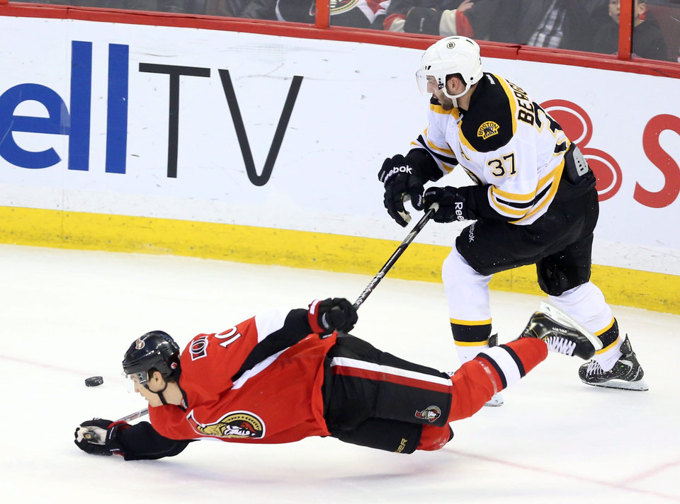 Ottawa Senator's Mike Lundin (10) dives for the puck as Boston Bruins' Patrice Bergeron (37) looks on during the first period of an NHL hockey game in Ottawa Thursday March 21, 2013.(AP Photo/The Canadian Press, Fred Chartrand)