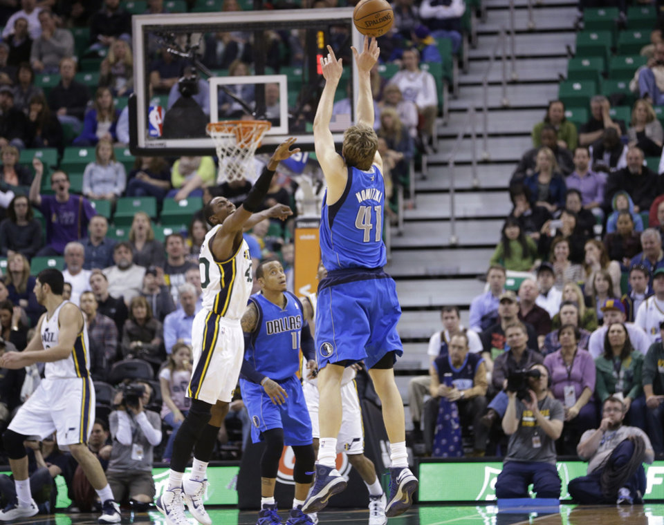 Photo - Dallas Mavericks' Dirk Nowitzki (41) shoots as Utah Jazz's Jeremy Evans defends in the second half during an NBA basketball game Wednesday, March 12, 2014, in Salt Lake City. The Mavericks won 108-101. (AP Photo/Rick Bowmer)