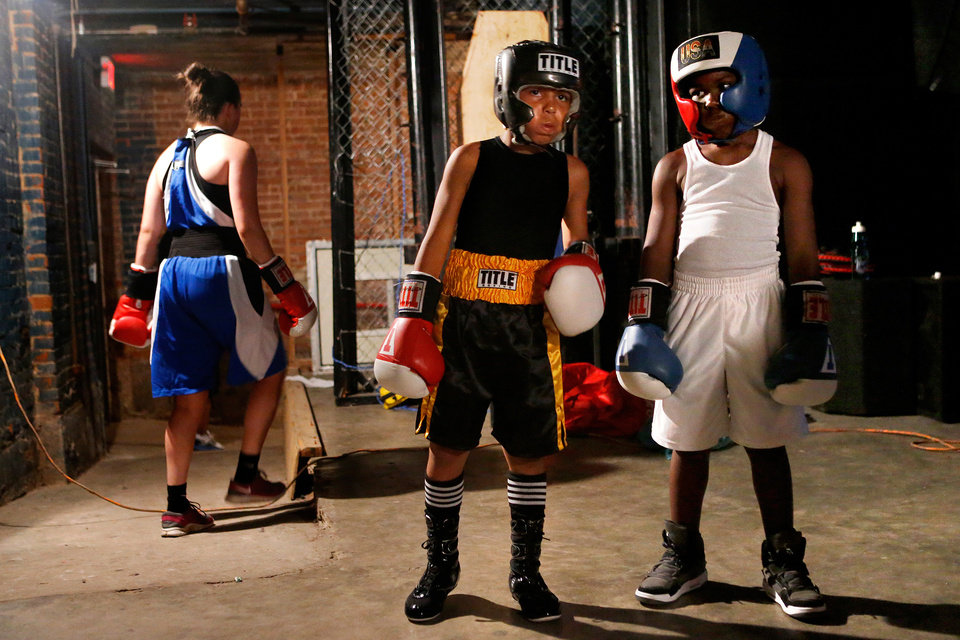 Photo -  Nine-year-old Chris Barba, of Edmond, left, stands next to Roderick Tisdale, 10, of Pawhuska, as they wait for their first fight at The Underground Arena in Oklahoma City, Saturday, June 15, 2013. Photo by Bryan Terry, The Oklahoman