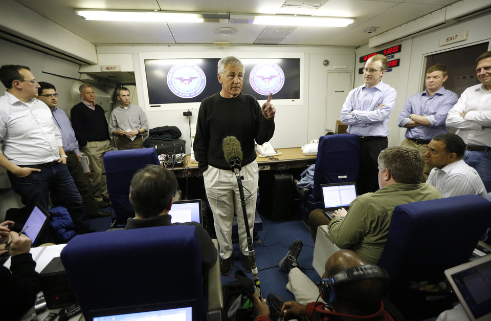 Photo - Defense Secretary Chuck Hagel speaks to the traveling press aboard his military aircraft, traveling between Andrews Air Force Base, Md. and Manas Air Force Base, Kyrgyzstan, en route to Afghanistan, Friday, March 8, 2013. Hagel arrived in Afghanistan Friday for his first visit as Pentagon chief, saying that there are plenty of challenges ahead as NATO hands over the country's security to the Afghans. (AP Photo/Jason Reed, Pool)