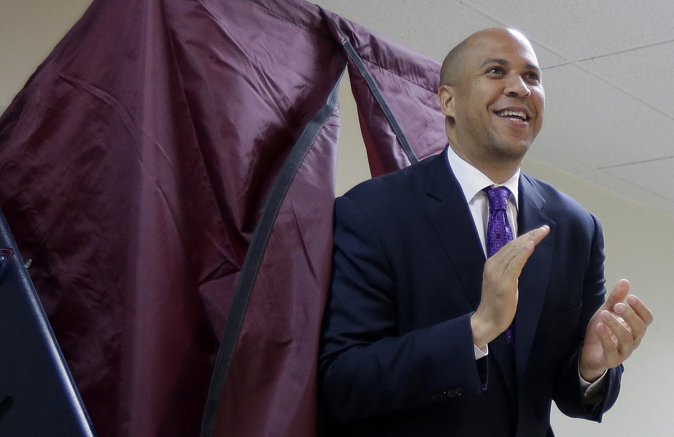 Photo - Newark Mayor Cory Booker walks out of a polling booth after casting his vote in a special election for the vacant New Jersey seat in the U.S. Senate, Wednesday, Oct. 16, 2013, in Newark, N.J. Booker is going up against Republican Steve Lonegan. (AP Photo/Julio Cortez)