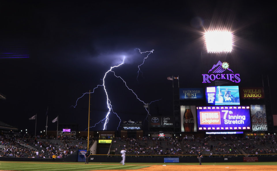 Photo - Lightning strikes in the background during the seventh inning of a baseball game between the Colorado Rockies and the San Diego Padres on Monday, July 7, 2014, in Denver. (AP Photo/Jack Dempsey)
