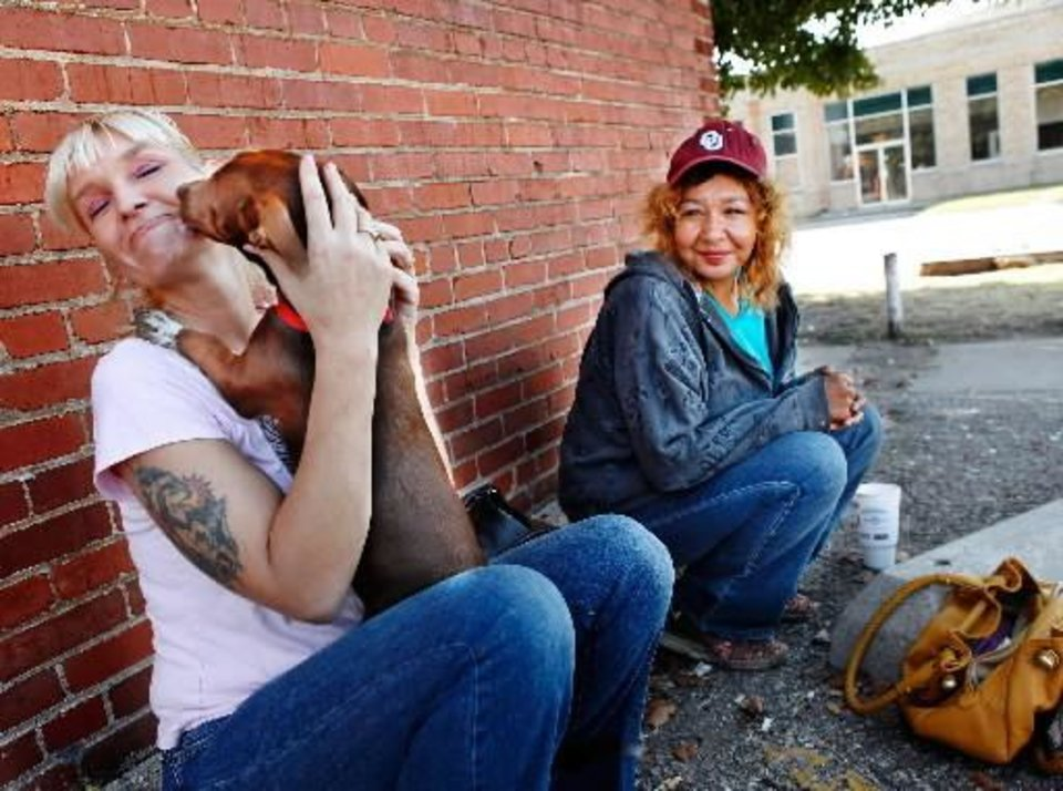 Photo - Melinda, 40, gets a lick from her friend's dog. The dog belongs to Edie Johnson, right. The women are sitting on parking blocks on the side of a building in the Film Row District. Many downtown homeless stay in the area along Sheridan, California and Reno between Walker and Western. Photo taken Wednesday, Oct. 21, 2010. Photo by Jim Beckel, The Oklahoman