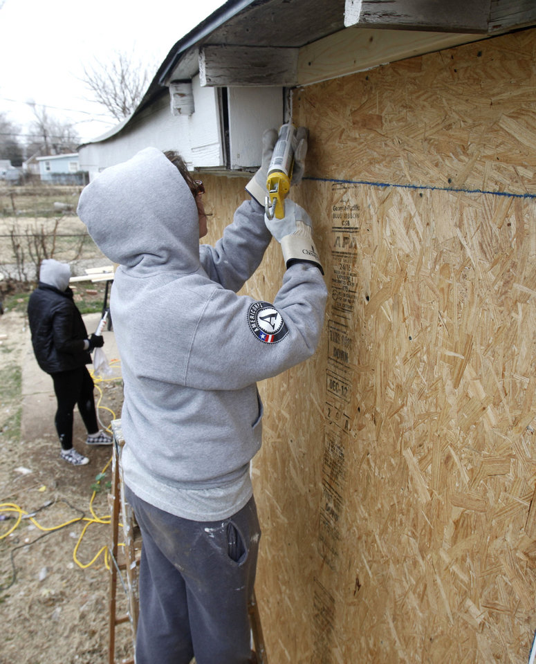 Julia Judge seals the seams in an exterior wall on a home at 2229 NE 21.   By Paul Hellstern, The Oklahoman <strong>PAUL HELLSTERN - Oklahoman</strong>