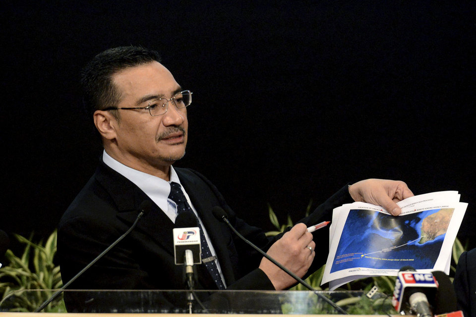 """Photo - FILE - In this Wednesday, March 26, 2014 file photo, Malaysia's Defense Minister and acting Transport Minister Hishammuddin Hussein shows a printout of the latest satellite image of objects that might be from the missing Malaysia Airlines plane, at Putra World Trade Center in Kuala Lumpur, Malaysia. Hussein has been pressed on whether there might be any survivors. He has said he was still """"hoping against hope"""" that passengers might be still found alive. This response was seen by some as contradictory to the Malaysian Airlines statement, creating a new discrepancy even on something which is fundamentally unknowable. (AP Photo/Joshua Paul, File)"""