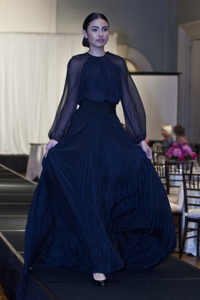 Photo - Model Adrianna S. is wearing a long-sleeve navy evening gown by Robin Brouilette at the Liberte runway show to benefit cystic fibrosis, hosted by Merrill Lynch Wealth Management.