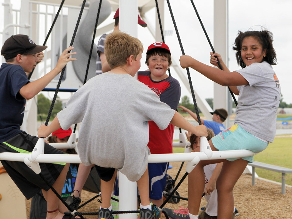 Photo - Children play on a merry-go-round during a camp at the Oklahoma River.  KT King - The Oklahoman