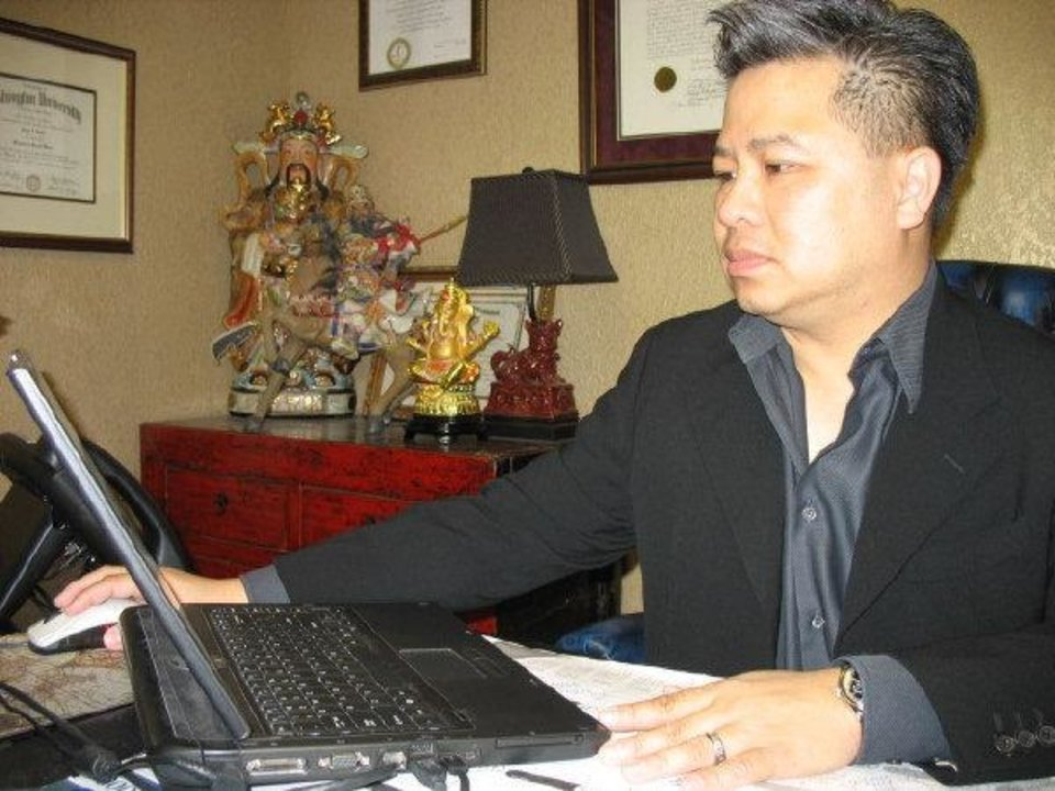 Photo - Lawyer Tuan Khuu works on his laptop Friday afternoon at his offices in Oklahoma City's Asian District. Khuu arrived in the city when he was six along with his parents.  Andrew Knittle