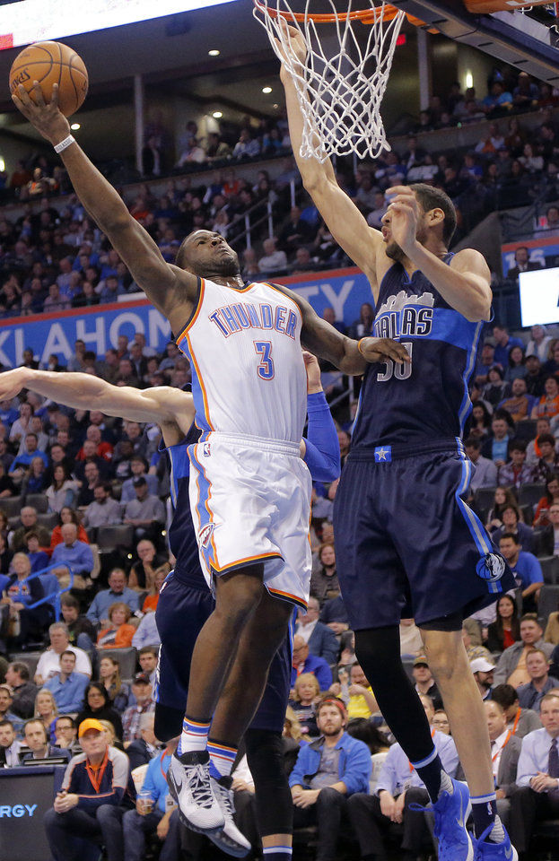Photo - Oklahoma City's Dion Waiters (3) drives to the basket against Dallas' Salah Mejri (50) during the NBA basketball game between the Oklahoma City Thunder and the Dallas Mavericks at Chesapeake Energy Arena on Wednesday, Jan. 13, 2016, in Oklahoma City, Okla.  Photo by Chris Landsberger, The Oklahoman