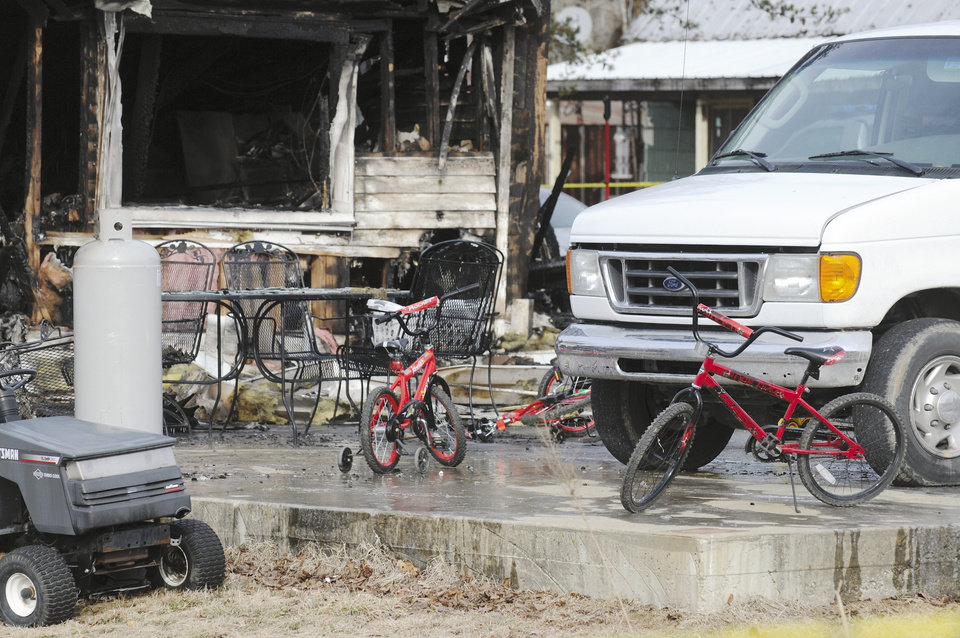 Photo - Childrens' bicycles sit in front of remains of home after an early morning fire in Greenville, Ky., Thursday Jan. 30, 2014.  Remains of 6 people have been recovered from the rubble and 3 additional people are missing.  (AP Photo/The Gleaner, Mike Lawrence)