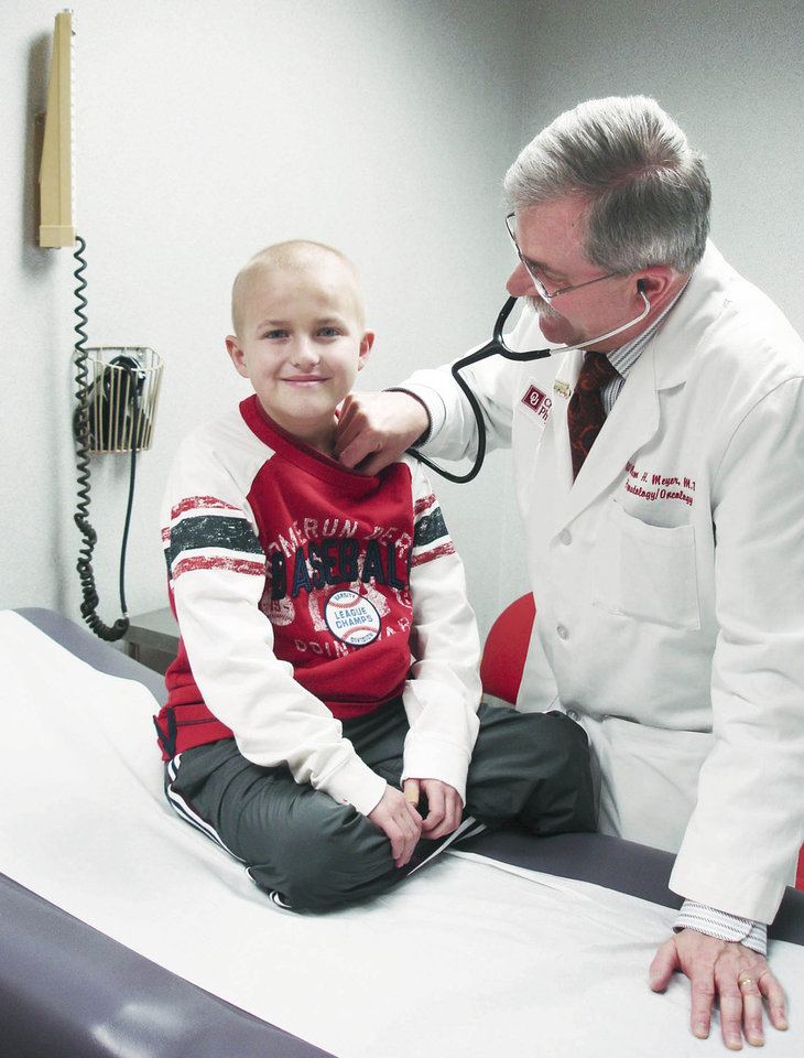 Mitchell Whitaker, left, is examined by Dr. William H. Meyer at the OU Medical Center. Whitaker, who died nearly two years ago at age 10 of leukemia, formed a special bond with the OU baseball team that continues to this day. Photo provided by OU Health Sciences Center