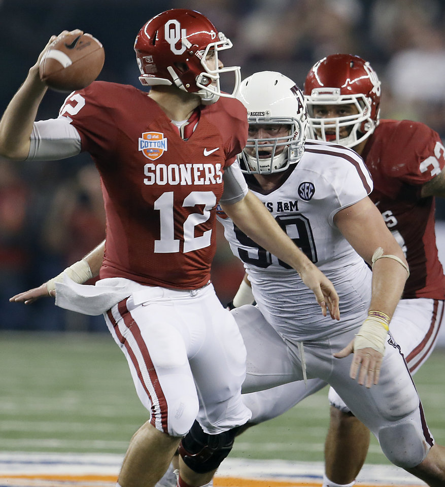 Texas A&M's Spencer Nealy (99) chases  Oklahoma's Landry Jones (12) during the college football Cotton Bowl game between the University of Oklahoma Sooners (OU) and Texas A&M University Aggies (TXAM) at Cowboy's Stadium on Friday Jan. 4, 2013, in Arlington, Tx. Photo by Chris Landsberger, The Oklahoman
