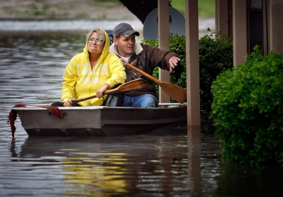 Photo - Crystal Goedereis and Chad Banks row through the Riverbend Apartments in West Memphis, Ark. Wednesday, April 27, 2011, as flood waters swamped the complex. West Memphis was declared a disaster area by the state as rains continued to pound the midsouth causing low lying areas to flood after a night of damaging winds toppled trees and damaged businesses. (AP Photo/The Commercial Appeal, Jim Weber)