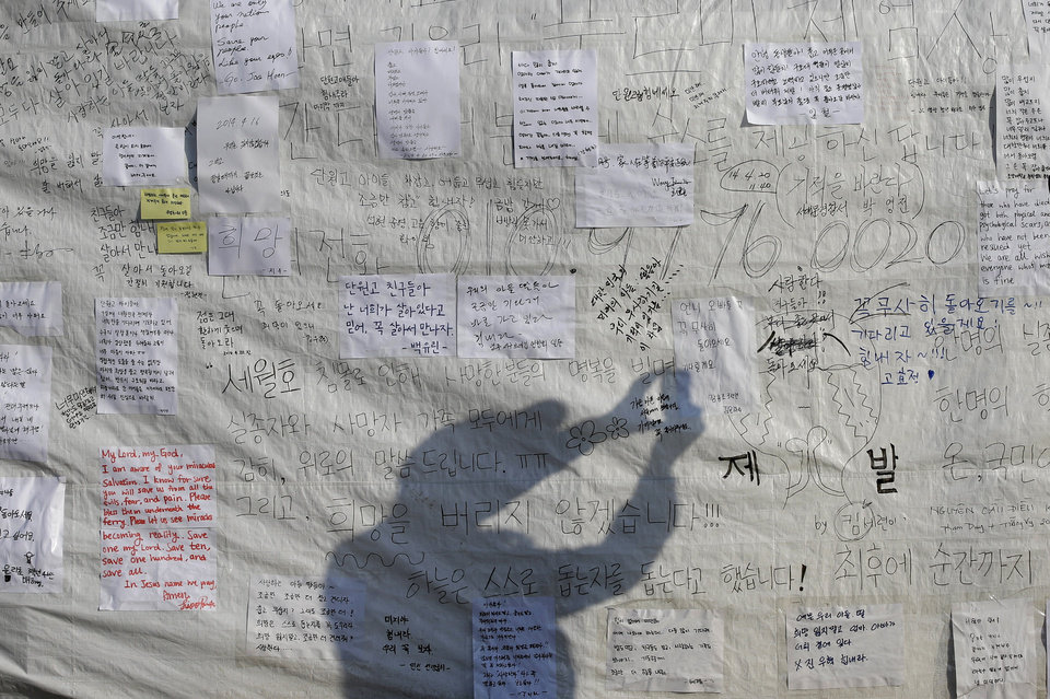 Photo - The shadow of a visitor taking a picture is cast on a board with messages wishing safe return of missing passengers aboard the sunken ferry Sewol at a port in Jindo, south of Seoul, South Korea, Tuesday, April 22, 2014. One by one, coast guard officers carried the newly arrived bodies covered in white sheets from a boat to a tent on the dock of this island, the first step in identifying a sharply rising number of corpses from a South Korean ferry that sank nearly a week ago. (AP Photo/Lee Jin-man)
