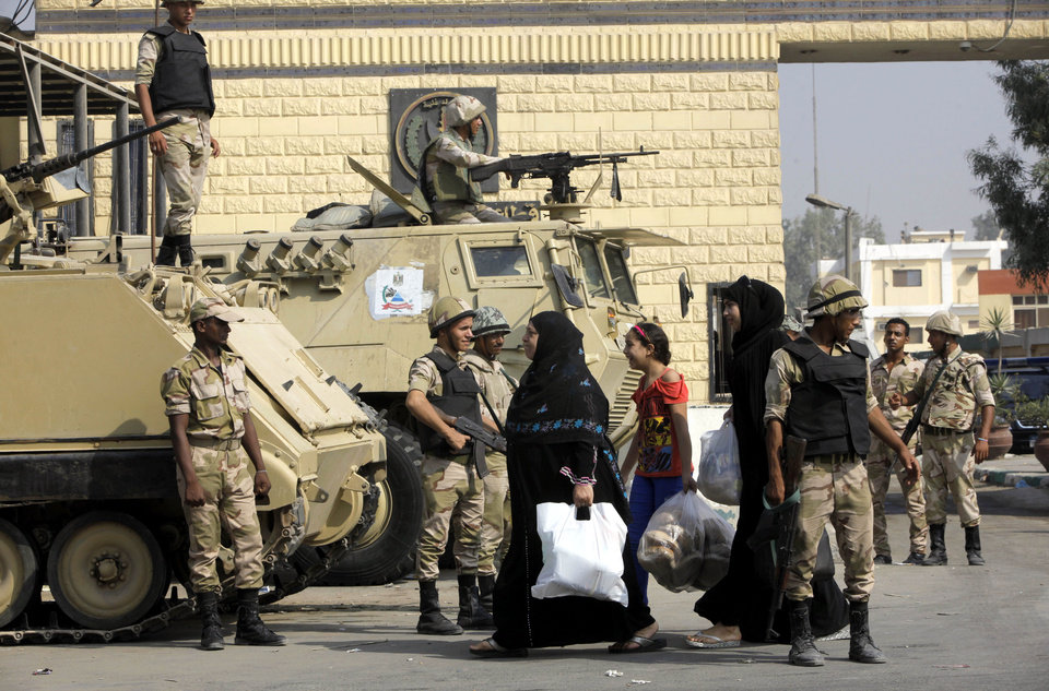 Photo - Women walk past soldiers guarding Torah prison, where Egypt's deposed autocrat Hosni Mubarak is held, in Cairo, Egypt, Thursday, Aug. 22, 2013. Mubarak is expected to be freed from prison and placed under house arrest on Thursday after being ordered released the previous day, following more than two years in detention. (AP Photo/Amr Nabil)