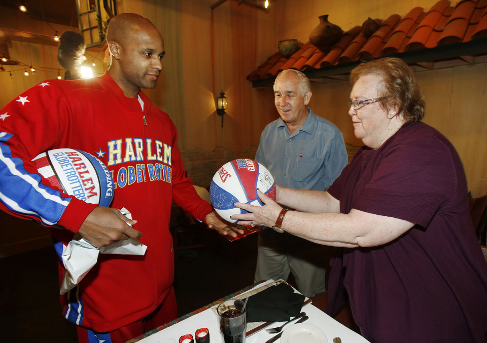 Harlem Globetrotter player Flight Time Lang gives an autographed basketball to George and Lin Wilson. Flight Time surprised Lin Wilson during a lunch date with her husband at Zio�s in Bricktown.