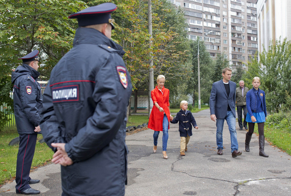 Photo - Russian opposition leader Alexei Navalny, second right, his wife Yulia, in red, walk with their children to a polling station as police officers stand guard in Moscow, Russia, Sunday, Sept. 8, 2013. Moscow is holding its first mayoral election in a decade. Although an incumbent backed by President Vladimir Putin is expected to win Sunday's election handily, the candidacy of charismatic opposition leader Alexei Navalny is changing Russian politics in ways that could pose a risk for the Kremlin in the months and years ahead. (AP Photo/Evgeny Feldman)