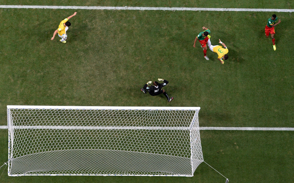 Photo - Brazil's Fred, left, scores his side's third goal during the group A World Cup soccer match between Cameroon and Brazil at the Estadio Nacional in Brasilia, Brazil, Monday, June 23, 2014. (AP Photo/Francois Xavier Marit, pool)