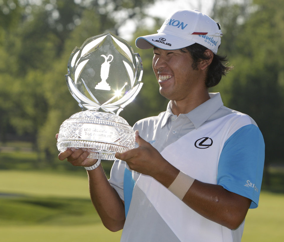 Photo - Hideki Matsuyama, of Japan, holds the trophy after winning the Memorial golf tournament on the first playoff hole Sunday, June 1, 2014, in Dublin, Ohio. (AP Photo/Jay LaPrete)