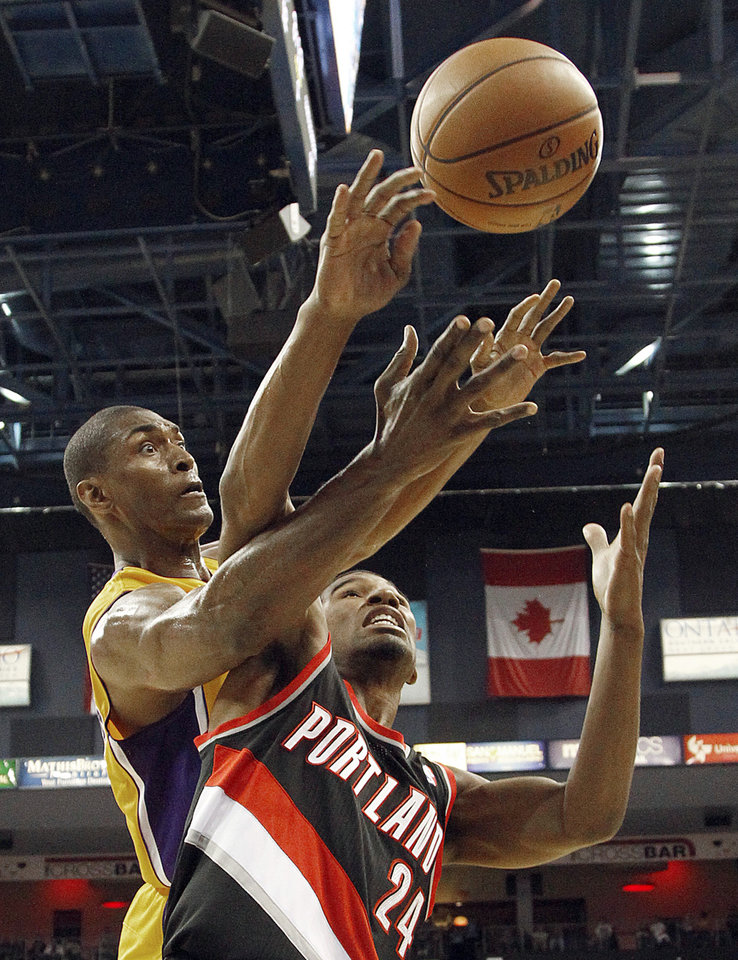 Los Angeles Lakers forward Metta World Peace, left, Portland Trail Blazers guard Ronnie Price battle for the ball in the second period of an NBA basketball preseason game in Ontario, Calif., Wednesday, Oct. 10, 2012. (AP Photo/Reed Saxon)