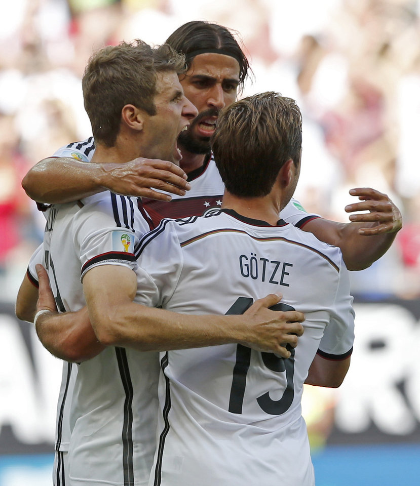 Photo - Germany's Thomas Mueller, left,  celebrates with Mario Goetze after scoring the opening goal during the group G World Cup soccer match between Germany and Portugal at the Arena Fonte Nova in Salvador, Brazil, Monday, June 16, 2014.   (AP Photo/Matthias Schrader)