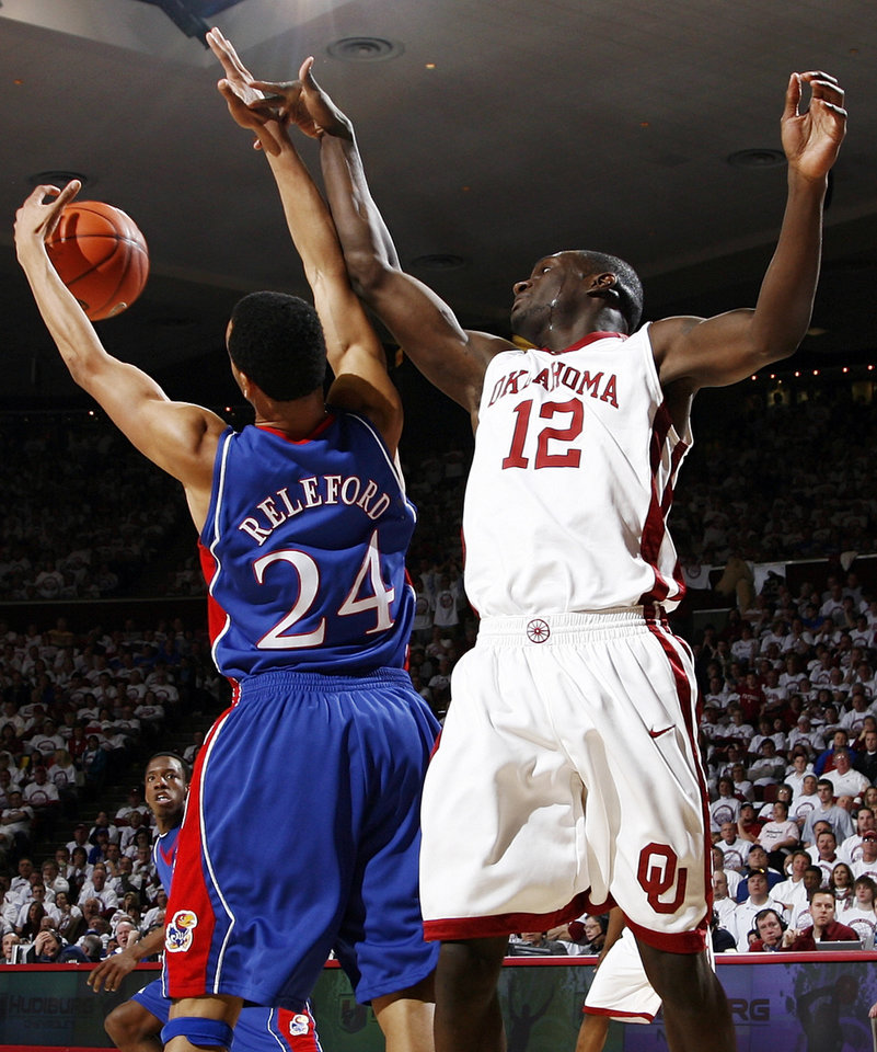 Photo - OU's Juan Pattillo (12) and KU's Travis Releford (24) battle for a rebound in the second half of the men's college basketball game between Kansas and Oklahoma at the Lloyd Noble Center in Norman, Okla., Monday, February 23, 2009. KU won, 87-78. BY NATE BILLINGS, THE OKLAHOMAN