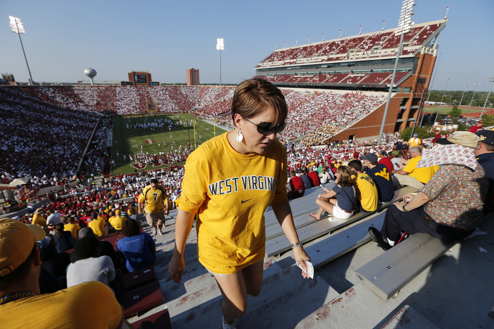 West Virginia fan Carla Hall takes her seat as fans file in on red and white day during a college football game between the University of Oklahoma Sooners (OU) and the West Virginia University Mountaineers at Gaylord Family-Oklahoma Memorial Stadium in Norman, Okla., on Saturday, Sept. 7, 2013. Photo by Steve Sisney, The Oklahoman