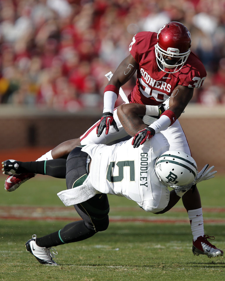 Photo - Oklahoma's Javon Harris (30) puts a hit on Baylor's Antwan Goodley (5) during the college football game between the University of Oklahoma Sooners (OU) and Baylor University Bears (BU) at Gaylord Family - Oklahoma Memorial Stadium on Saturday, Nov. 10, 2012, in Norman, Okla.  Photo by Chris Landsberger, The Oklahoman