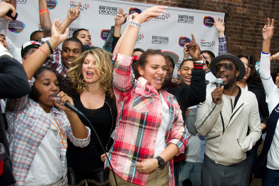 The Black Eyed Peas members Fergie, second left, and will.i.am, right, sing with students at the launch of a new Peapod Adobe Youth Voices Academy in New York, Tuesday, April 19, 2011. (AP Photo/Charles Sykes)
